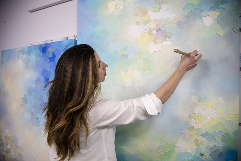 Abstract artist Melissa McKinnon painting in her art studio